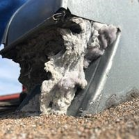 side view of a dryer vent with lint falling out